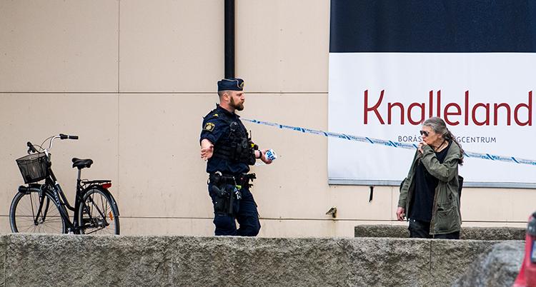 En polis och en till person framför avspärrande band utanför byggnaden.