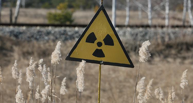 en skylt som visar fara för radioaktiva ämnen på en öde plats vid Tjernobyl.