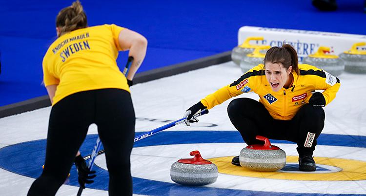 Från en match i curling. Knochenhauer följer med stenen. Hasselborg sitter inne i boet och skriker. De har gula tröjor på sig.