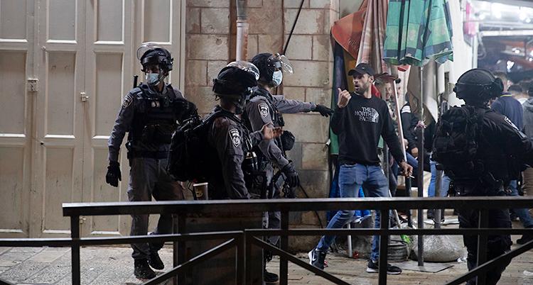 Från en gata i staden Jerusalem. Fyra poliser försöker få bort en ung man från platsen. En av poliserna knuffar på mannen. Poliserna har hjälmar på sig. Mannen har en keps.