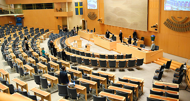 En bild från den stora salen i riksdagens hus. Några politiker har samlats.