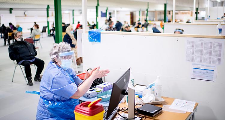 En stor curlinghall har blivit till en central för vaccin. Människor sitter på stolar och väntar på sin tur. Närmast i bild syns en sköterska. Hon har blå skyddskläder och skydd för ansiktet.