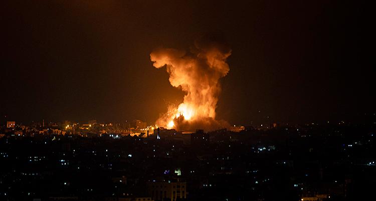Det är natt i Gaza. Det är mörkt. Man ser ljus från fönster. Långt bort är det en explosion. Det kommer eld och rök.