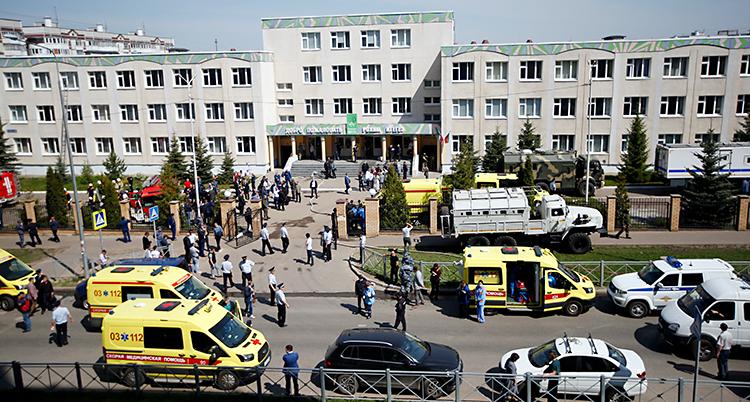 Bilden är tagen utanför en stor skola. Skolan är grå. På vägen utanför skolan finns flera ambulanser och polisbilar. Många människor är också där.