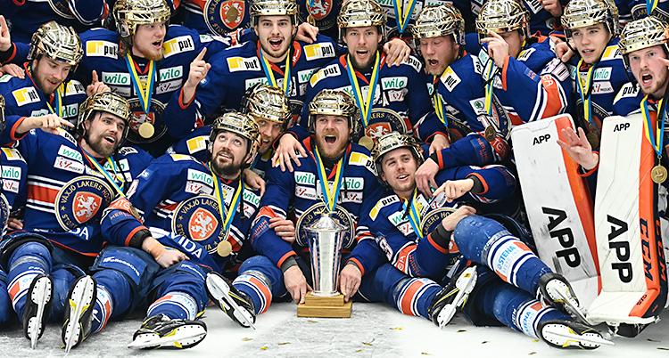 Hela Växjös lag är samlat på isen. De är glada och firar. De har guldhjälmar på sig. Pokalen står i mitten, på isen.