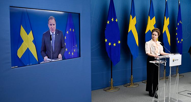 Från en träff med journalister. Stefan Löfven pratar på en skärm på en vägg. Till höger om skärmen står minister Amanda Lind. Hon står vid en talarstol med en mikrofon. Bakom henne finns svenska flaggor.