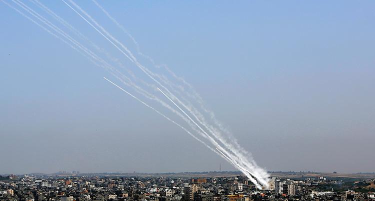 En bild på Gaza uppifrån. Från ett hus skjuts det stridsraketer. Man ser långa vita streck av rök.
