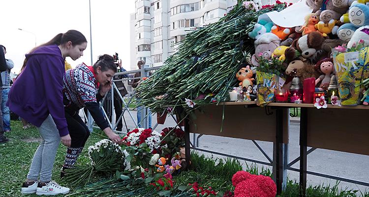 En flicka och en kvinna lägger ner blommor. På platsen finns det massor av blommor och gosedjur.