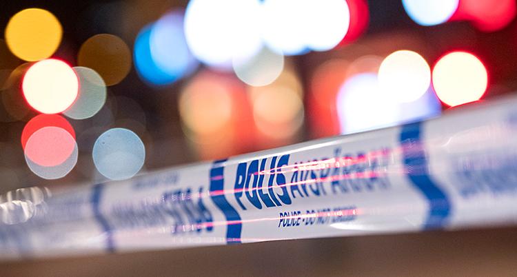Det är kväll. Poliser har satt upp ett band som spärrar av en plats. I bakgrunden syns suddiga ljus från staden.
