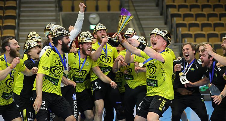 Bilden är tagen i en sporthall. Flera män står tillsammans och jublar. De håller i en pokal. De har gula tröjor och guldhjälmar på huvudet.