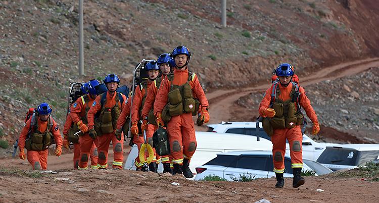 Bilden är tagen utomhus. Vi ser räddningsarbetare som går för att leta efter människor. Arbetarna har på sig röda overaller och blå hjälmar.