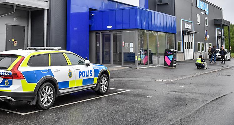 En polisbil står parkerad vid ett köpcentrum. En polis sitter på huk vid en ingång.