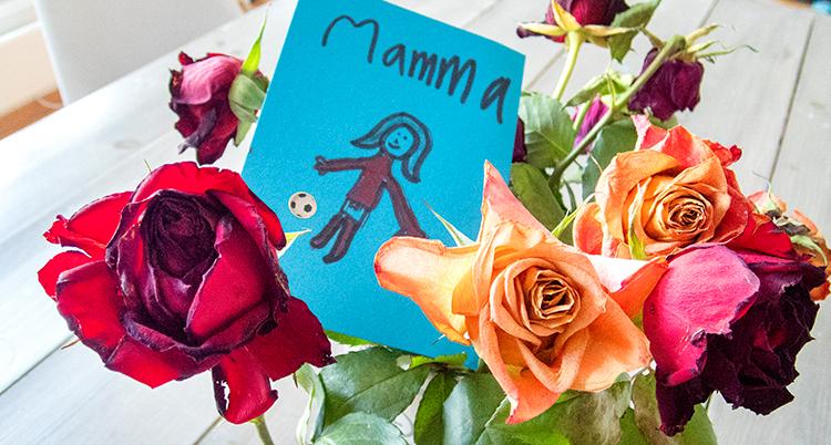 ett kort som det står mamma och en ritad figur, gjort av ett barn, ligger bland en bukett rosor.