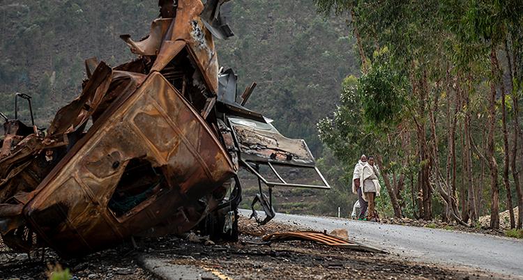 Bilden är tagen vid en väg. Närmast i bilden ligger en bil som är bränd och förstörd. Längre bort står två män och tittar på bilen.