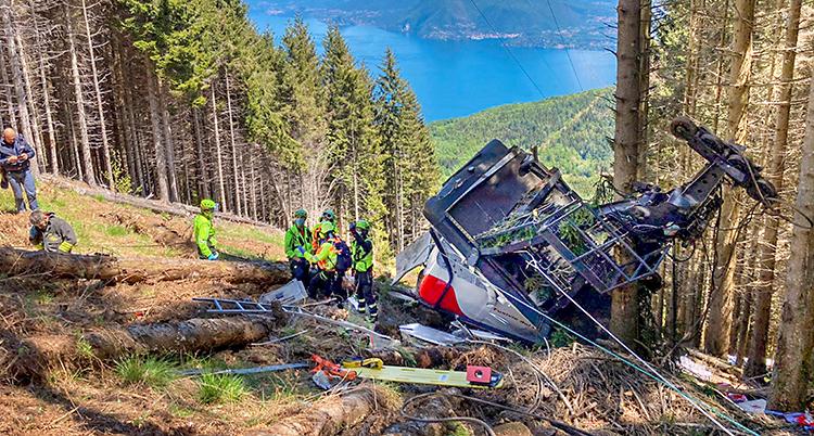 En vagn från en linbana ligger på marken. Den är trasig. Räddningspersonal står vid vagnen.