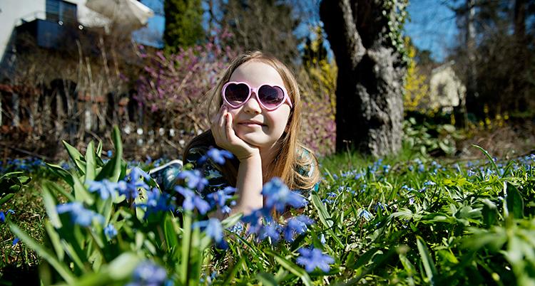 En flicka ligger i gräset och solar. Det är blå blommor i gräset. Flickan har på sig solglasögon som ser ut som hjärtan.