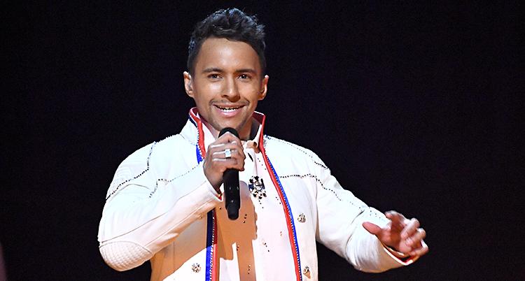 Han står på en scen och sjunger i en mikrofon. Han har på sig en samisk dräkt som är vit.