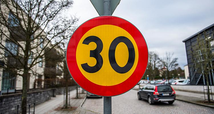 En förbudsskylt där det står 30. Bakom den är en gata med bilar.