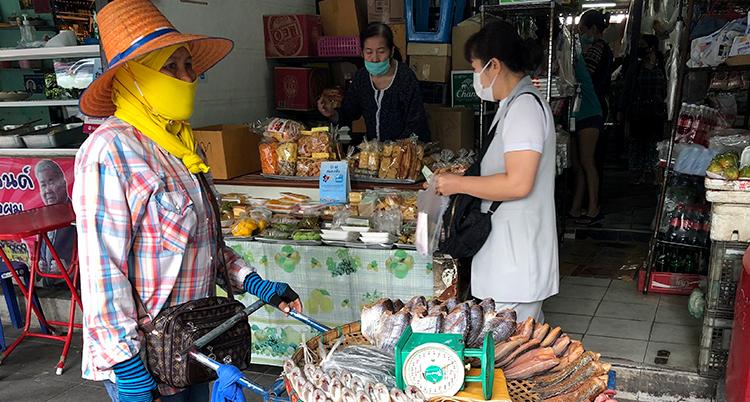 Tre kvinnor syns på marknaden. De har alla munskydd.
