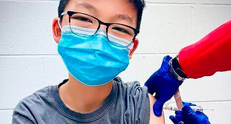 En ung pojke med mörkt hår, glasögon och blått munskydd tittar in i kameran. En person med lila handskar och röd ärm ger honom en spruta i vänster arm, där hans grå t-shirt är uppdragen