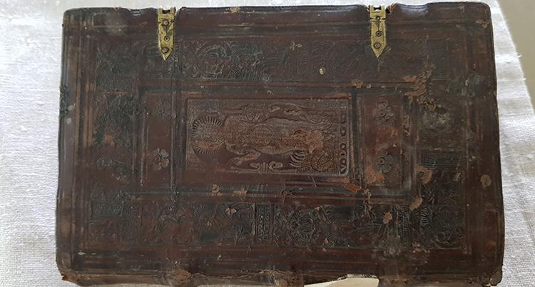 En gammal brun bok ligger på ett vitt underlag.