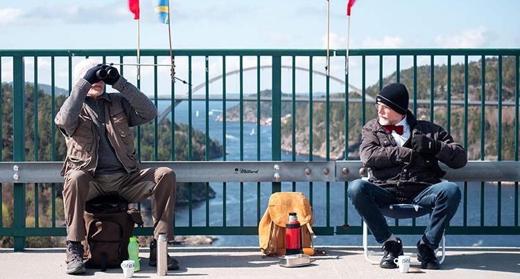 två män sitter på varsin stol på en bro. Havet syns bakom staketet. Han till vänster tittar i en kikare. Båda har ytterkläder och mössor. Framför dem står termosar och muggar.