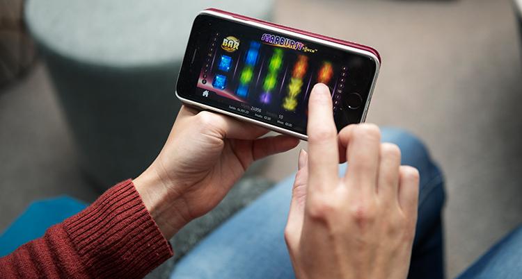 En person håller i en mobil och drar med höger pekfinger över skärmen. Han spelar ett spel i ett onlinecasino.