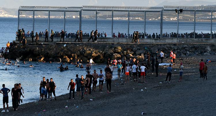 Massor av människor vid det höga staketet som skiljer länderna åt.