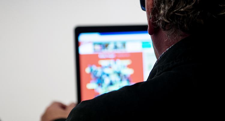 En personer sitter med en dator framför sig.