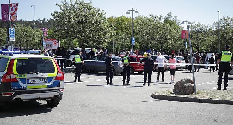 En parkeringsplats med flera bilar. Poliser i gula västar syns och platsen är avspärrad med tejp.