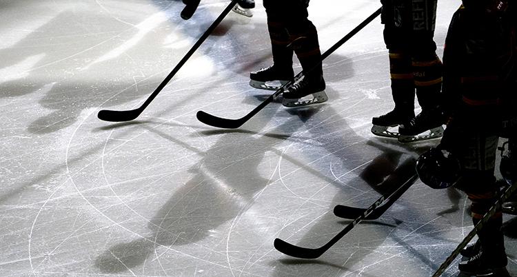 Ishockeyspelare med klubbor på isen. Bara deras skridskor och klubbor syns.