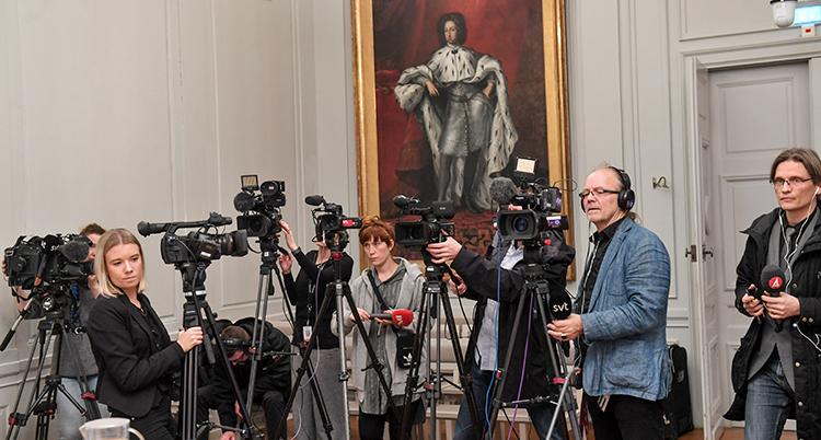 journalister trängs med flera mikrofoner och tv-kameror i ett rum.