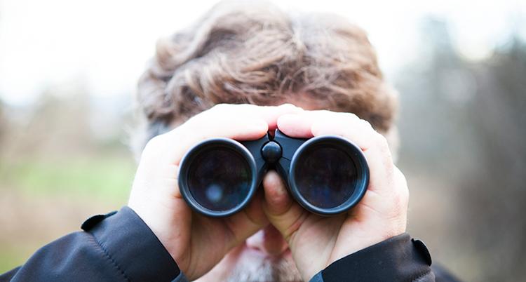 Han håller båda händerna runt kikaren och håller den framför ögonen och tittar in i kameran.