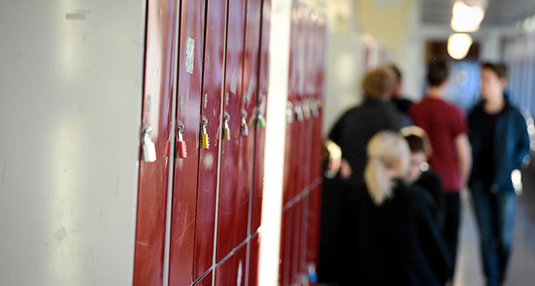 En korridor med flera elever. Några skåp syns på bilden.