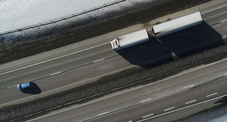 En lastbil och en bil kör på en motorväg. Bilden är tagen ovanifrån.
