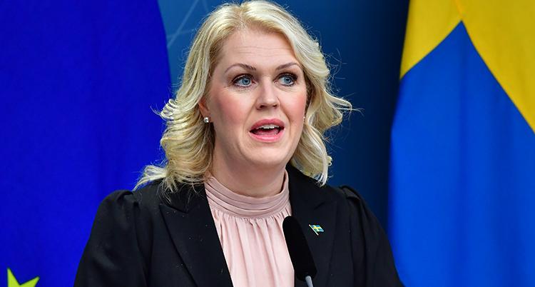 En närbild när Lena Hallengren pratar. Hon tittar bredvid kameran. Bakom henne syns en del av en svensk flagga.