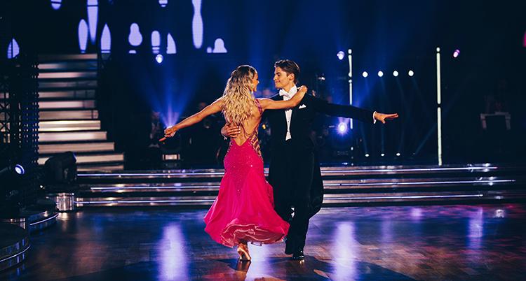 De dansar, han i mörk kostym, hon i rosa klänning. De håller om varandra och sträcker ut armarna.