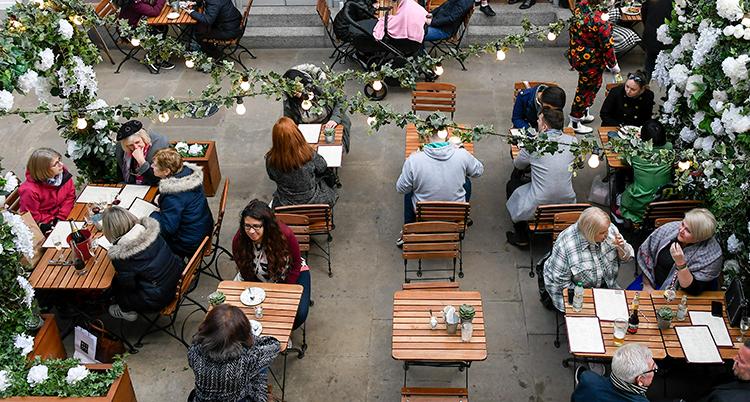 En bild tagen ovanifrån på flera människor som sitter vid bord.