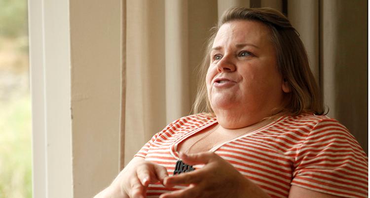 Hon tittar mot vänster ur ur bilden och gör en gest med händerna. Hon har randig tröja och hår som är bortstruket från ansiktet.