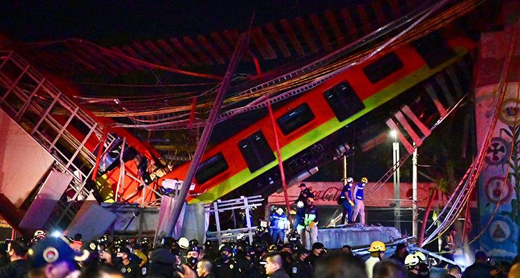 Det är kväll på bilden. Många människor syns. Det röda tåget hänger ner från bron.