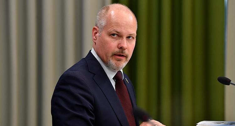 En nära bild på ministern. Han tittar år sidan och är allvarlig.