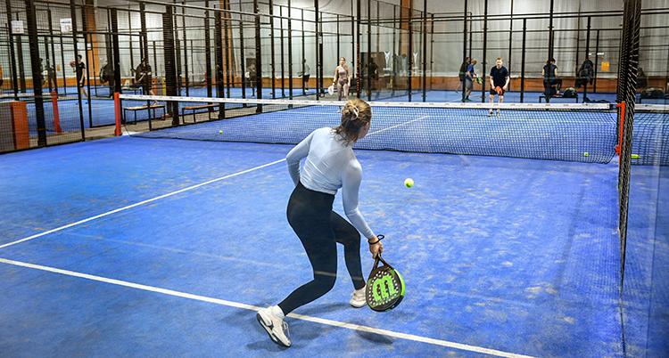 En spelare är på väg att slå en boll med sitt racket. Planen är blå.