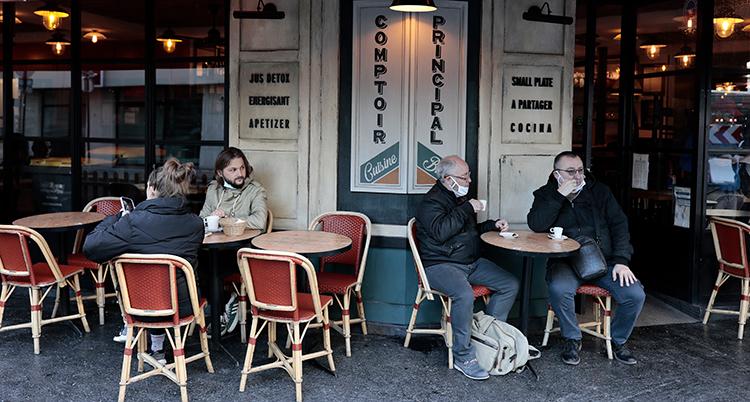 Två människor sitter på en servering utomhus. Ett bord bredvid är tomt. Sedan sitter två andra vid nästa bord.