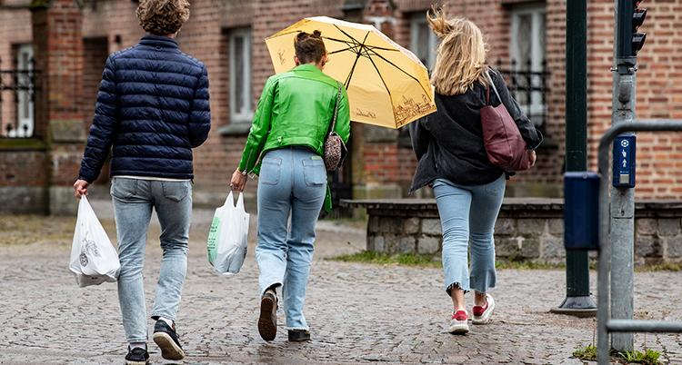 personer som går och håller i plastpåsar.
