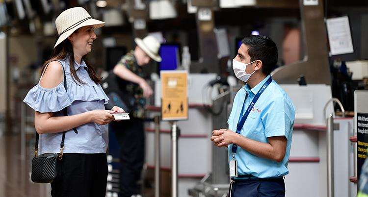 En kvinna i en solharr står vid en kontrollant. Han har munskydd. De pratar med vandra.