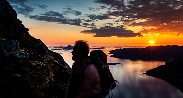 En vacker solnedgång i bakgrunden. En man klättrar på ett berg i förgrunden, vi ser bara siluhetten.