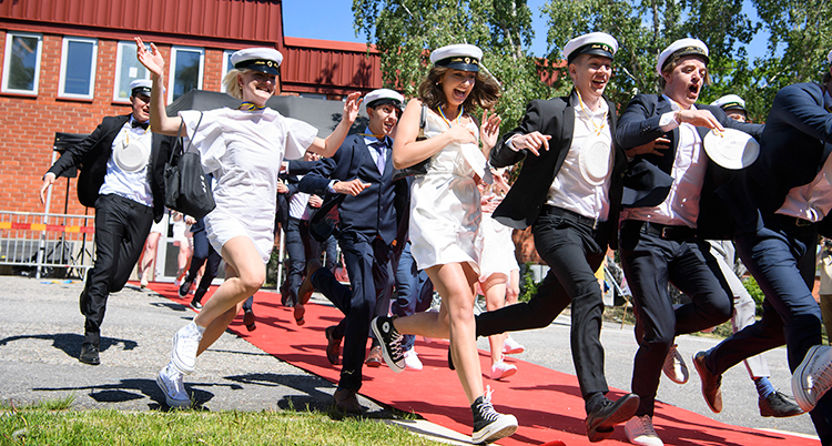 De springer ut på en röd matta i klänningar och kostymer med studentmössor på huvudet. De springer mot kameran, med en tegelröd skola bakom.