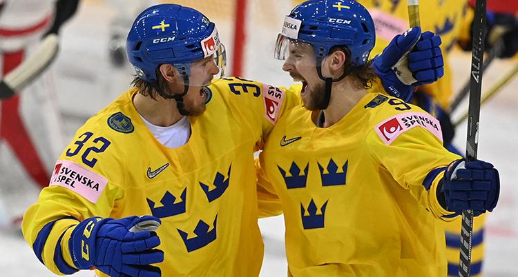 Två spelare tittar på varandra och skrattar. De är på väg att krama varandra.