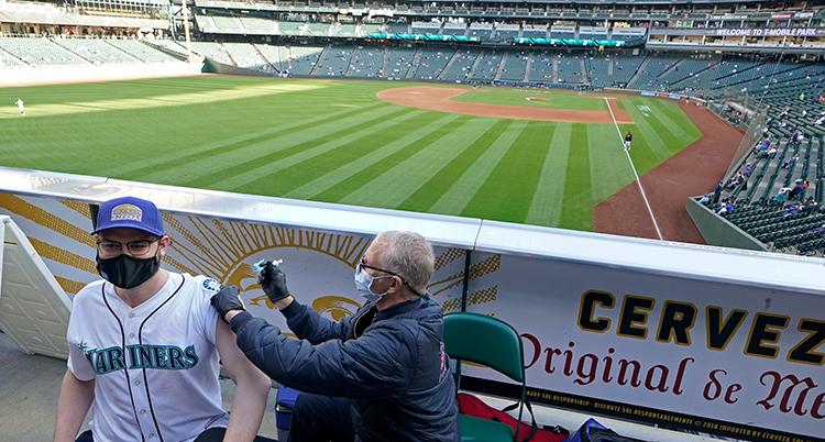 Han syns till vänster i bild med vit tröja och får en spruta i armen av en man med handskar och jacka. De är på en baseballarena med läkare i bakgrunden.