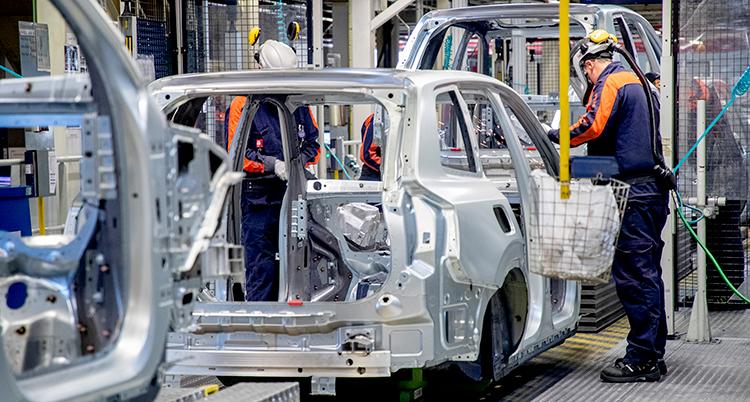 Två personer i hjälmar och arbetskläder jobbar med att montera på en bilkaross i en fabrik